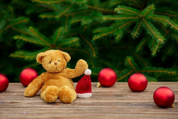 Osito de peluche y gorro de navidad en mesa de madera con ramas de abeto en el fondo