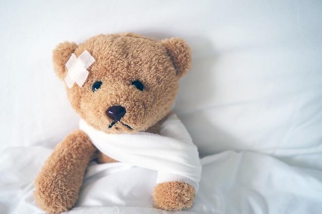 Oso de peluche acostado enfermo en la cama con una diadema y un paño cubierto