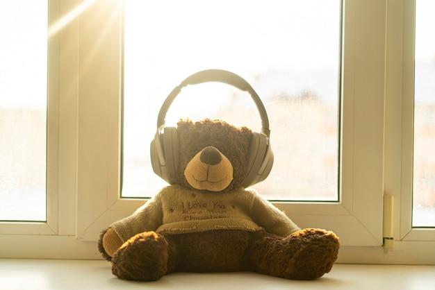 Un oso de peluche en auriculares escucha la radio de música de audio.