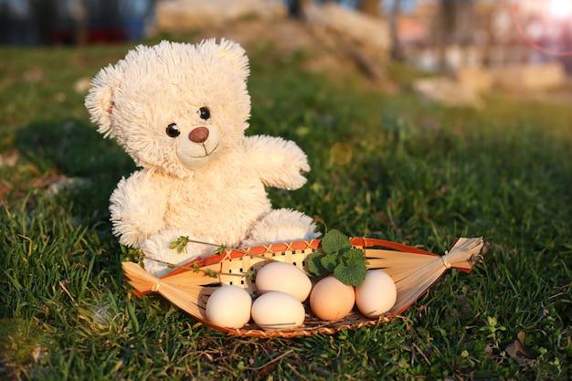 Oso de peluche blanco se sienta en la hierba verde junto a una caja de madera con huevos.