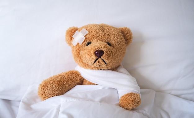 Oso de peluche cayó enfermo en la cama, herido por el accidente.