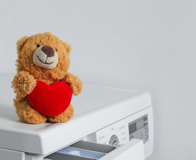 Oso de peluche con un corazón rojo en una lavadora