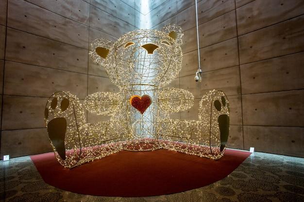 Oso de peluche hecho de luces en un edificio.
