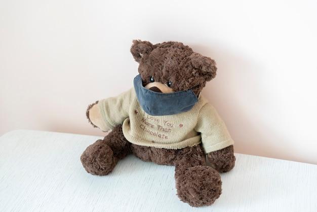 Un oso de peluche de juguete con una mascarilla protectora, concepto de epidemia de coronavirus