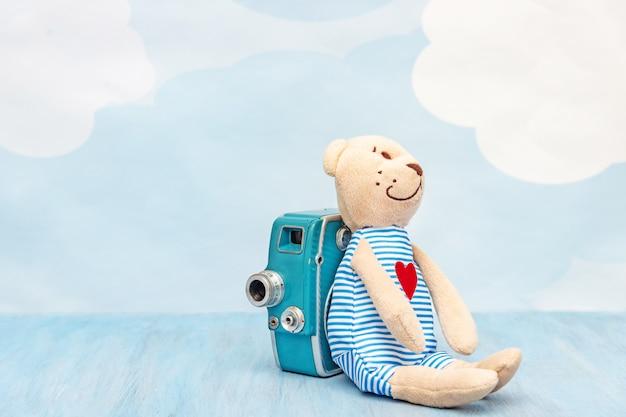 Oso de peluche de juguete de peluche se sienta cerca de la cámara de vídeo retro en un azul.