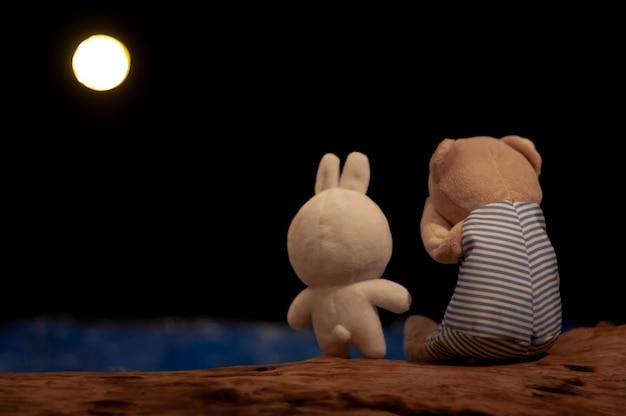 Oso de peluche llorando y muñeca de conejo dando consuelo.