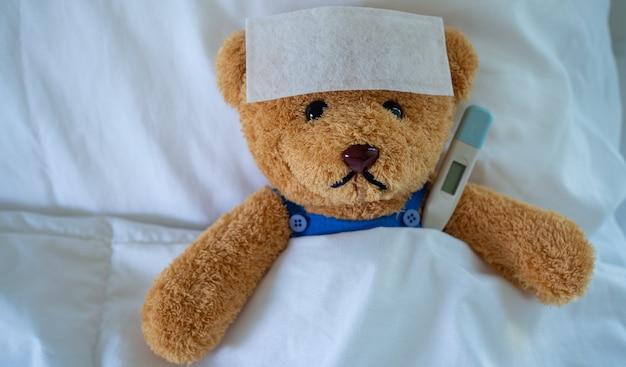 Oso de peluche marrón con fiebre en la cama