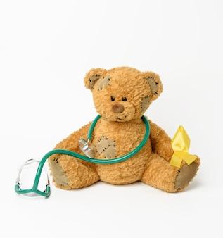 Oso de peluche marrón con parche, cinta amarilla de seda en forma de lazo sobre fondo blanco, concepto de la lucha contra el cáncer infantil, problema de los suicidios y su prevención