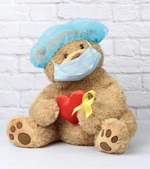 Oso de peluche marrón sostiene en su pata una cinta amarilla doblada en un lazo, concepto de la lucha contra el cáncer infantil. problema de los suicidios y su prevención