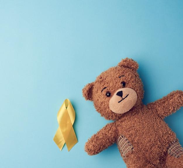 Oso de peluche marrón tiene en su pata una cinta amarilla doblada en un bucle sobre un fondo azul. concepto de lucha contra el cáncer infantil