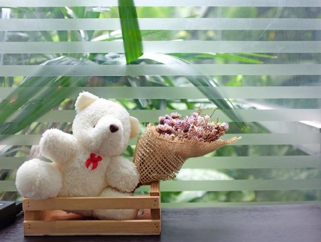 Oso de peluche muñeca con flor de hierba seca en la mesa cerca de ventanas de vidrio.