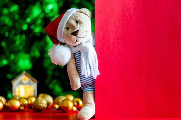 Oso de peluche de santa claus se encuentra al lado de la tarjeta roja vacía con adornos coloridos y fondo de árbol de navidad.