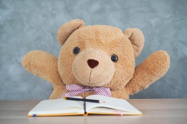 El oso de peluche se sienta en la mesa y levanta la mano.