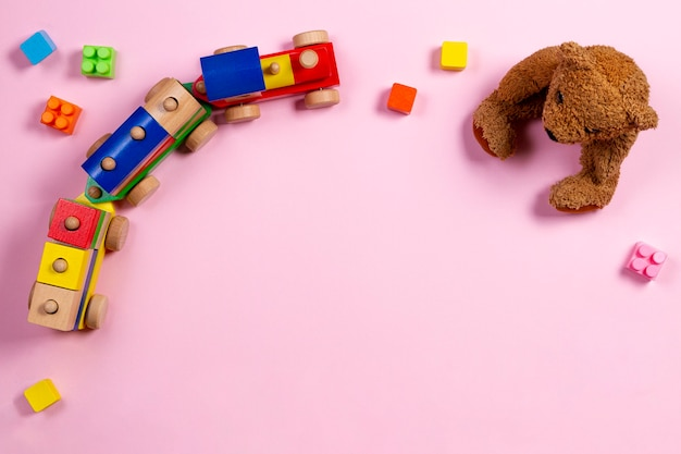 Oso de peluche, tren de juguete de madera y bloques de colores sobre fondo rosa claro. vista superior