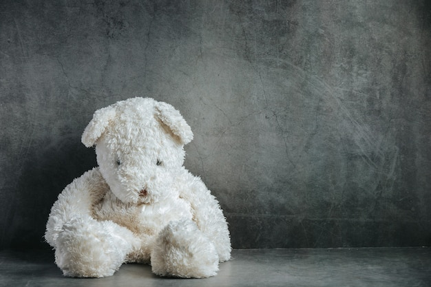 Oso de peluche triste en una habitación vacía