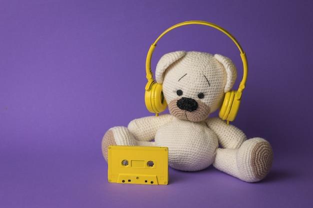 Un oso de punto blanco con auriculares amarillos sobre un fondo morado.