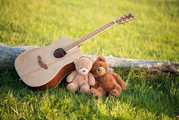 Osos de peluche enamorados en la hierba con una guitarra en un día soleado de verano. concepto de amor y fidelidad.