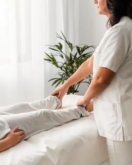 Osteópata femenina tratando las piernas de un paciente