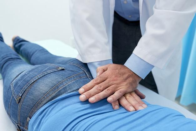 Osteópata recortada que ajusta la espalda del paciente con masaje