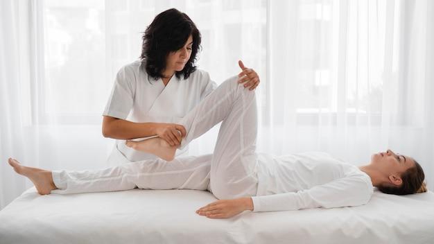 Osteópata tratando a una mujer joven en el hospital.