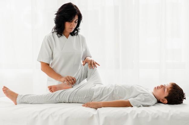 Osteópata tratando a un niño dándole un masaje en el hospital.