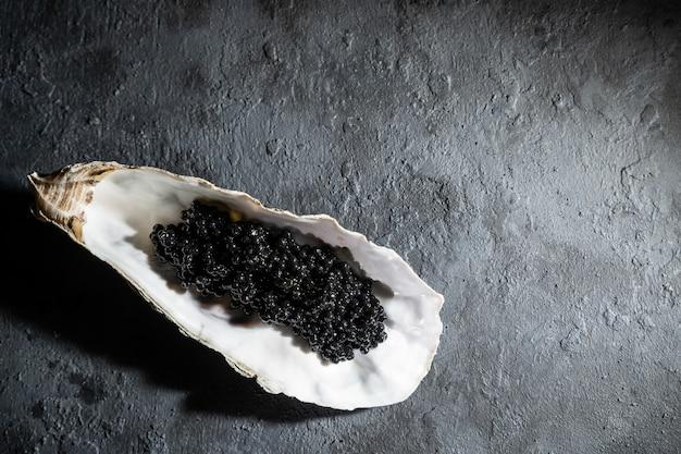 Ostras abiertas con caviar de esturión negro mesa de hormigón negro. vista superior, plano, copia espacio.