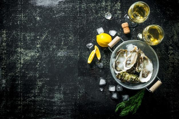 Ostras abiertas en un colador con vino blanco, rodajas de limón y cubitos de hielo sobre la mesa rústica negra