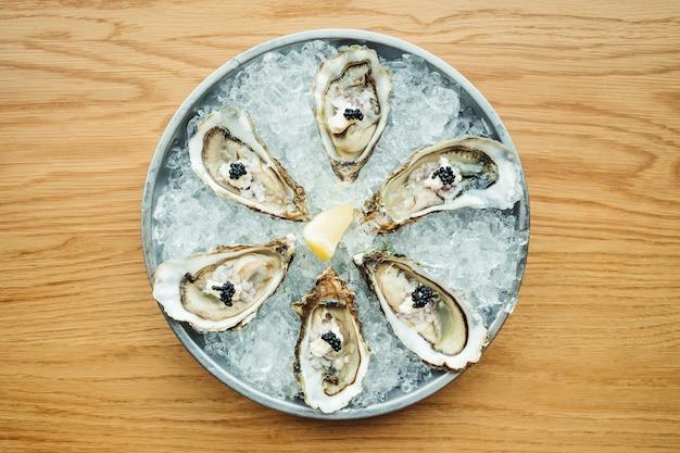 Ostras crudas y frescas con caviar encima y limón.