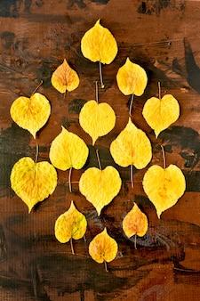 Otoño árbol amarillo deja en una mesa de madera hola otoño