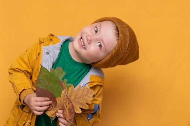 Otoño. bebé sonriente con hojas amarillas en la mano. moda estacional. ropa de otoño moda infantil. hoja cae. niño en ropa dorada, sombrero naranja
