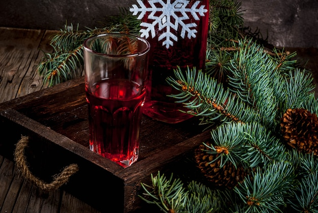 Otoño, bebidas de invierno. jugo de arándano casero, en una botella y vasos sobre una vieja mesa rústica de madera, con ramas de árboles de navidad.