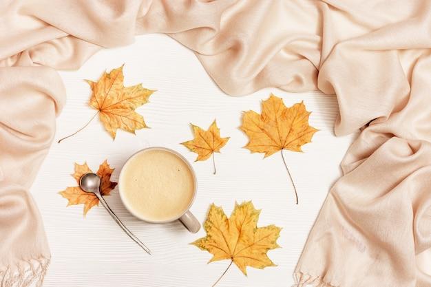 Otoño composición acogedora con hojas secas de arce y bufanda beige pastel, taza de café y cuchara de metal sobre fondo de madera blanca. otoño, concepto de otoño. vista plana, vista superior.