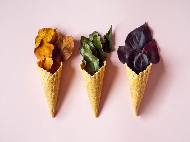 Otoño composición plana laico de tres conos de helado con hojas de varios colores sobre fondo rosa