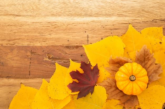 Otoño fondo de acción de gracias con calabazas naranjas y hojas caídas en mesa de madera