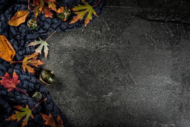 Otoño fondo de piedra oscura con otoño rojo y amarillo deja cálido suéter o manta y pequeñas calabazas, vista superior copia espacio