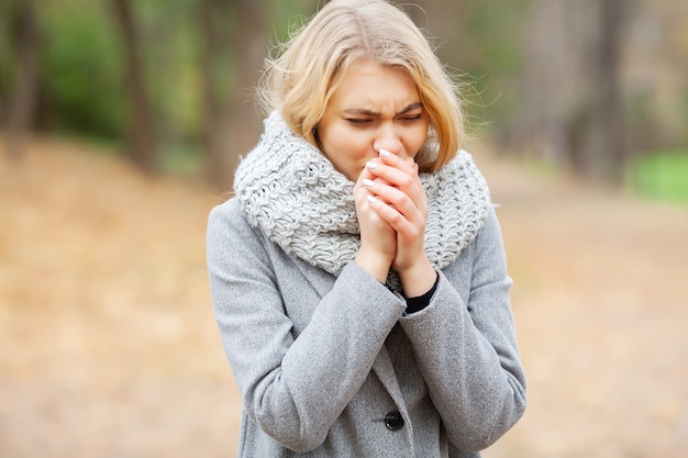 Otoño frío mujer vistiendo mascarilla y sosteniendo pastillas entre árboles florecientes en el parque