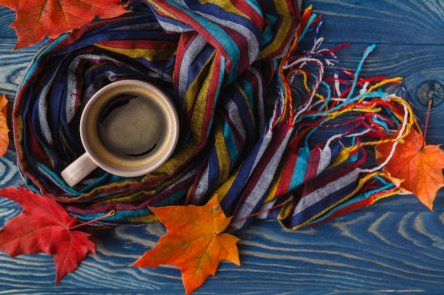 Otoño, hojas de otoño, una taza de café humeante y una bufanda caliente sobre la superficie de la mesa de madera