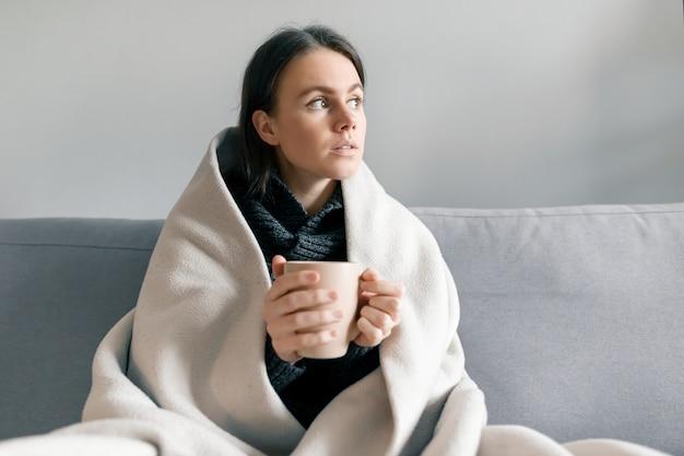 Otoño invierno retrato de joven con taza de bebida caliente, bajo una manta caliente