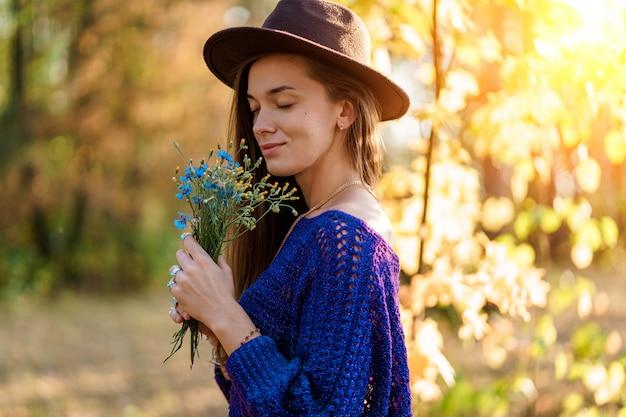 Otoño mujer morena con el pelo largo con un sombrero marrón y un suéter azul de punto disfruta del aroma de las flores silvestres en el bosque de otoño al aire libre en otoño