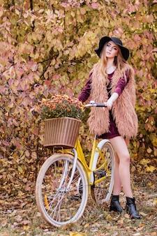 Otoño niña en un paseo con una bicicleta amarilla y una canasta de flores