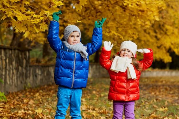 Otoño de los niños en el parque. los niños juegan en la naturaleza.