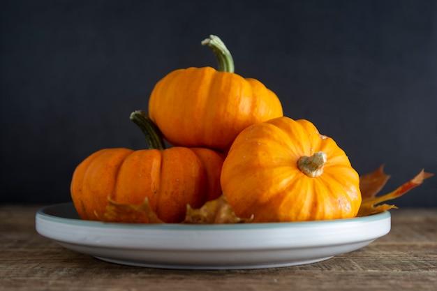 Otoño, otoño, acción de gracias con calabaza naranja en plato sobre madera rústica