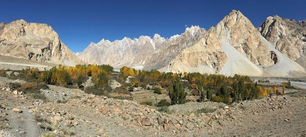 Otoño en passu muestra un cielo azul claro y álamos rodeados de montañas