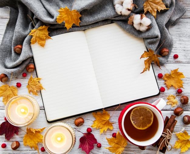 Otoño plano con cuaderno, taza de té y hojas.