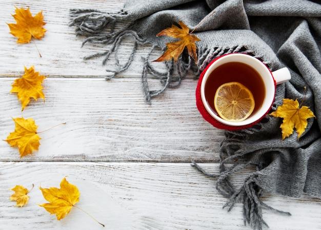 Otoño plano con taza de té y hojas.