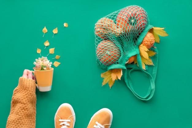 Otoño plano yacía sobre fondo azul claro. naranja calabazas en bolsa de malla. taza con hojas de arce amarillas en manos femeninas en suéter naranja y zapatillas de lona.