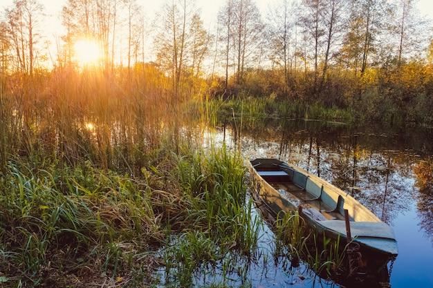 Otoño puesta de sol en el río con un barco en primer plano