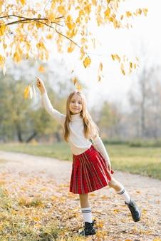 Otoño retrato abierto de una hermosa niña feliz caminando en un parque o bosque.