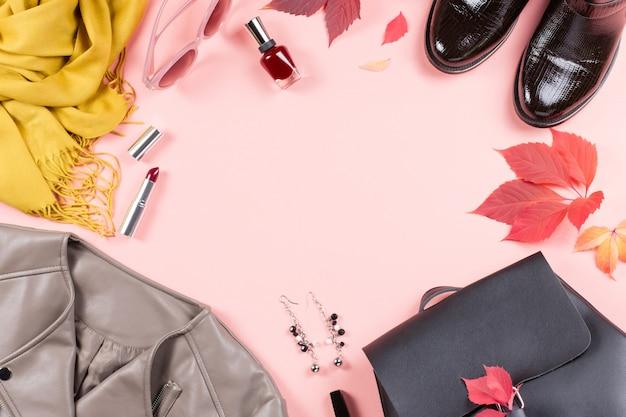 Otoño ropa femenina sobre fondo rosa con hojas