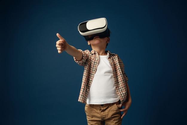 Otra visión del mundo. niño o niño en jeans y camisa con gafas de casco de realidad virtual aisladas sobre fondo azul de estudio. concepto de tecnología de punta, videojuegos, innovación.